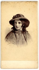 A young woman wearing a cloak and hat, smiling slightly.