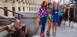 Fashionistas pose for photographs in front of a homeless man outside Moynihan Station following a showing of the Rag & Bone Spring/Summer 2013 collection during New York Fashion Week