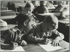 Children / pupils writing on paper with a pen in the classroom. The Netherlands, location unknown. [1937].