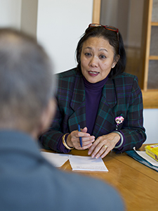 Tufts Medical Center interpreter Yoshie Ng gathers medical history from a patient.
