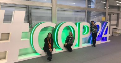 Mieke, Kelly, and Fang standing in front of the COP24 sign, which is illuminated with green and blue lights