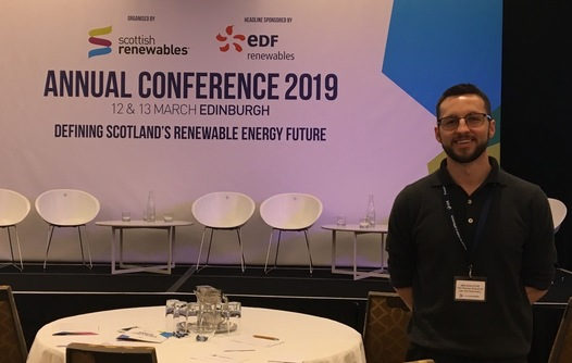 """Iain standing to the right of a round table, with a stage in the background that has white chairs and a backdrop reading """"Annual Conference 2019"""""""