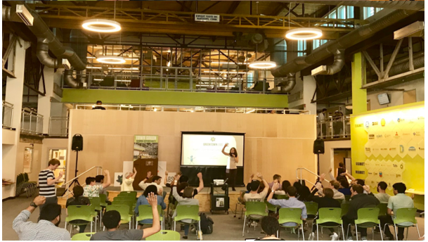 Photo of a presentation in an industrial space, attendees are sitting in green chairs and raising their hands as someone stands in front of a screen speaking into a microphone
