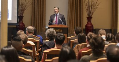 Photo of Adnan Amin standing at a podium in front of a room of seated people, speaking into a microphone
