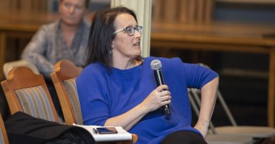 Photo of Kelly Sims Gallagher leaning back in a chair, speaking into a microphone