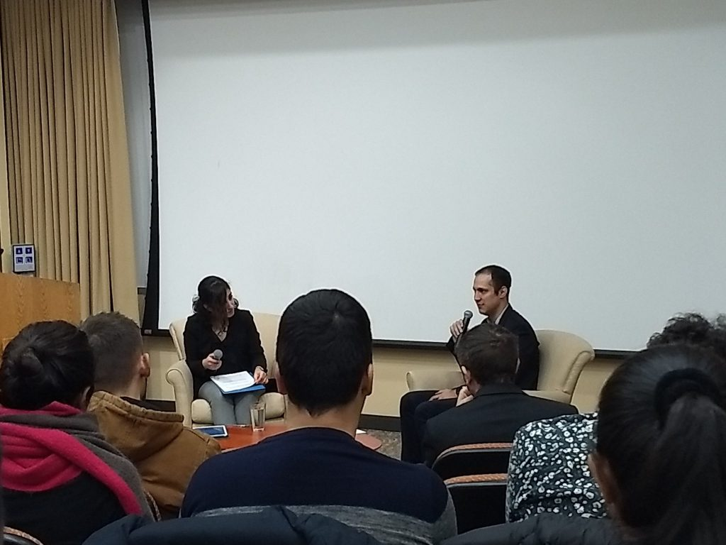 student interviews speaker in front of audience