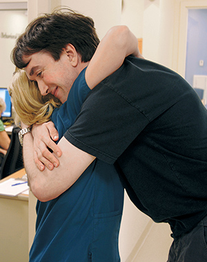 Michael Hancock of Boylston, Massachusetts, gives hygienist Laura Dombroski a hug after his cleaning at the TDF clinic in Worcester. Photo: Matthew Modoono