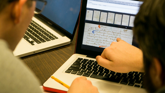 Students analyzing text on a laptop