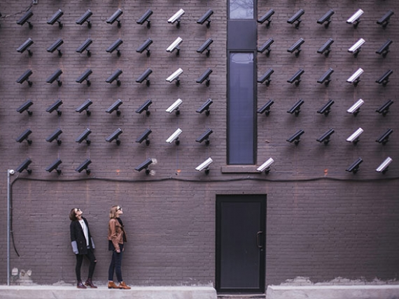 Two people stand below dozens of security cameras on the side of a building