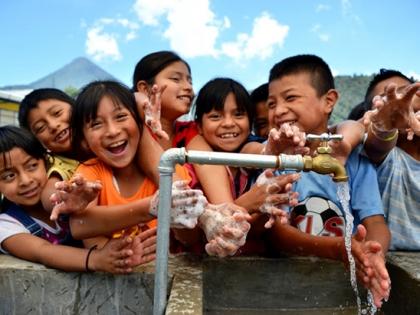 Children wash hands and smile
