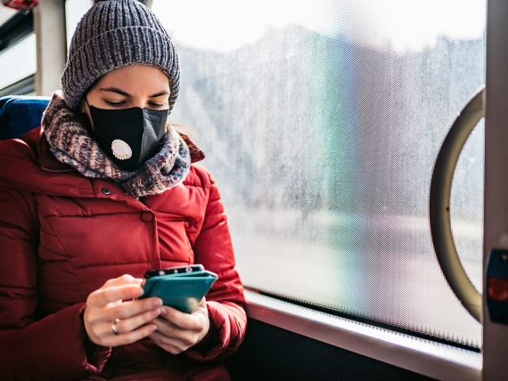 Woman with face mask and cellphone rides public bus