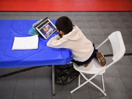 Child uses tablet while sitting at a table