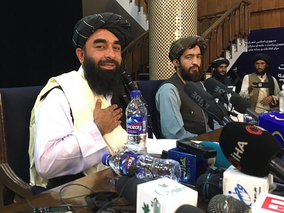 TOPSHOT - Taliban spokesperson Zabihullah Mujahid (L) gestures as he arrives to hold the first press conference in Kabul on August 17, 2021 following the Taliban stunning takeover of Afghanistan. (Photo by Hoshang HASHIMI / AFP) (Photo by HOSHANG HASHIMI/AFP via Getty Images)
