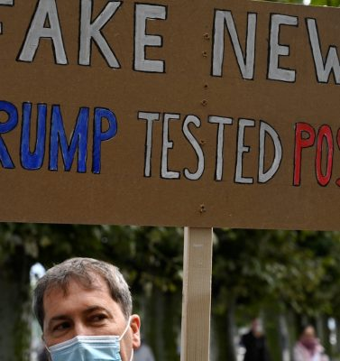 A demonstrator holds up a placard reading 'Fake news - (US President Donald) Trump tested positive' to protest against masks and virus restrictions during the ongoing Covid-19 pandemic (novel coronavirus) in Konstanz, southern Germany, on October 3, 2020. (Photo by SEBASTIEN BOZON / AFP) (Photo by SEBASTIEN BOZON/AFP via Getty Images)