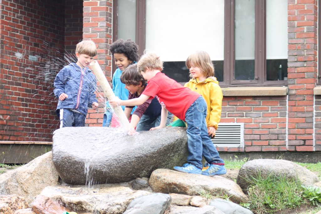 group of children playing with water shooting out of hold on rock formation in play yard