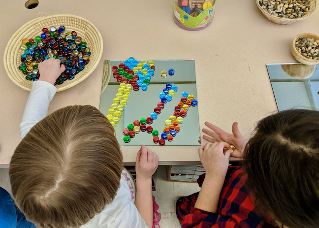 two children forming flowers using colorful stones