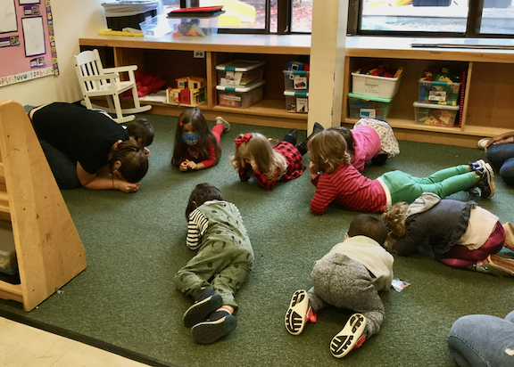 teacher and children curled up on floor to strike meditation pose