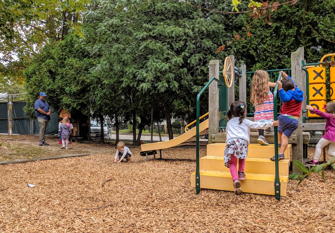 a group of children climbing up steps of playground structure, one child touching the mulch ground cover, and in background teacher talking to a group of children