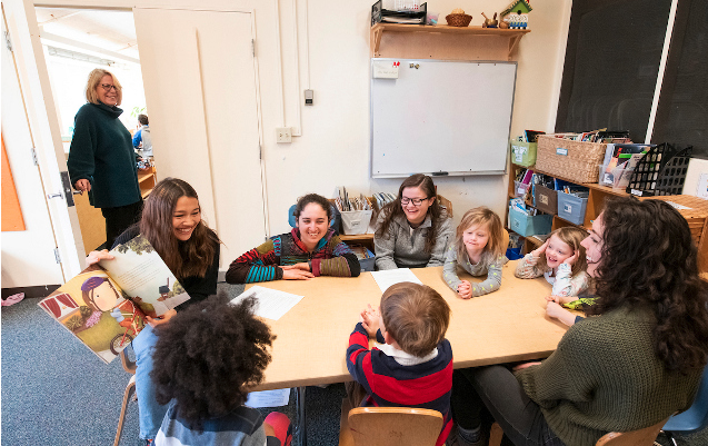 """Professor Susan Russinoff checks in on the group reading and discussion on friendship as EPCs children and the Professor Russinoff's undergraduate students share the book, """"Enemy Pie."""" Photo: Alonso Nichols"""