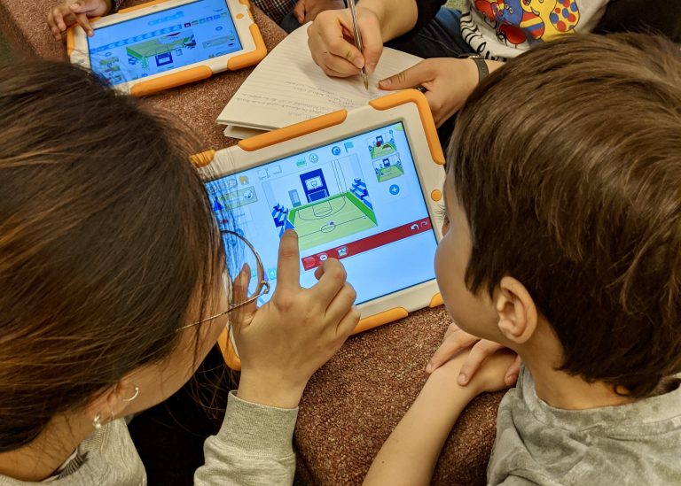 An undergraduate student, enrolled in a course investigating technology tools for playful learning, shows one of our curious learners how the Scratch Jr. app works.