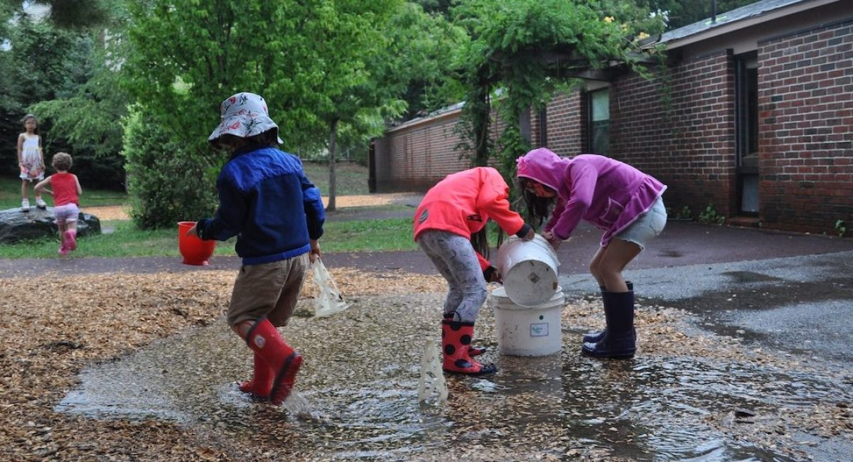 three children scoop water from big rain puddle & pour into large buckets