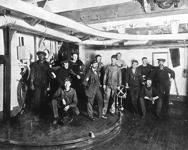 """Gunner's Gang"", photographed in one of the ship's torpedo rooms. Halftoned photograph, published in Uncle Sam's Navy, 1898. Credit: U.S. Naval Historical Center Photograph # NH 50183."