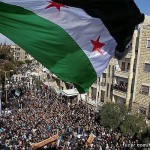 Syria independence flag flies over a large gathering of protesters in Idlib, Syria. Photo: flickr.com/freedomhouse