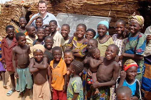 Fletcher alumnus Joshua Haynes (MIB '10), now a senior development technologist and media advisor at USAID, pictured with children of villagers in Niger attending a mobile literacy workshop. Credit: Joshua Haynes 2009