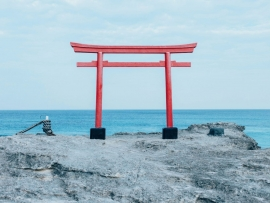 Red Japanese Gate/Archway on Rocks Overlooking Beach