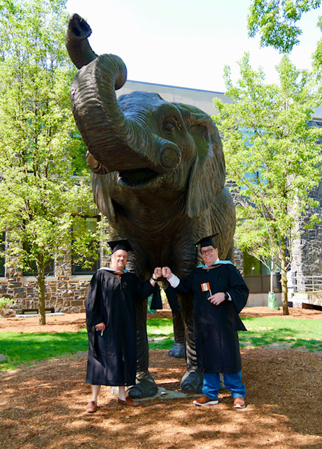 Eric S. and Bill H. are wearing their graduation cap and gowns and giving a fist bump to each other in front of the Tufts University Jumbo sculpture