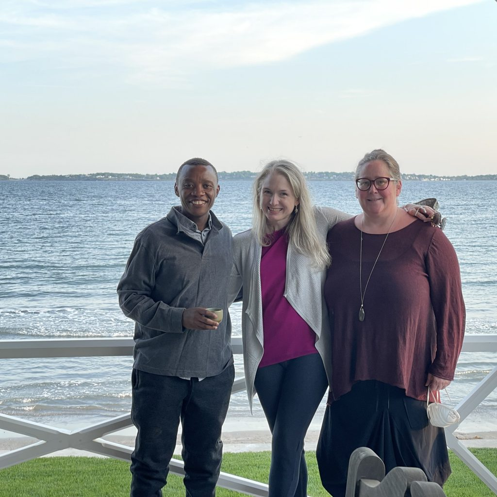 From left to right, Dieudonne R., Sarah W., and friend Lindsay W. standing in front of a water vista.