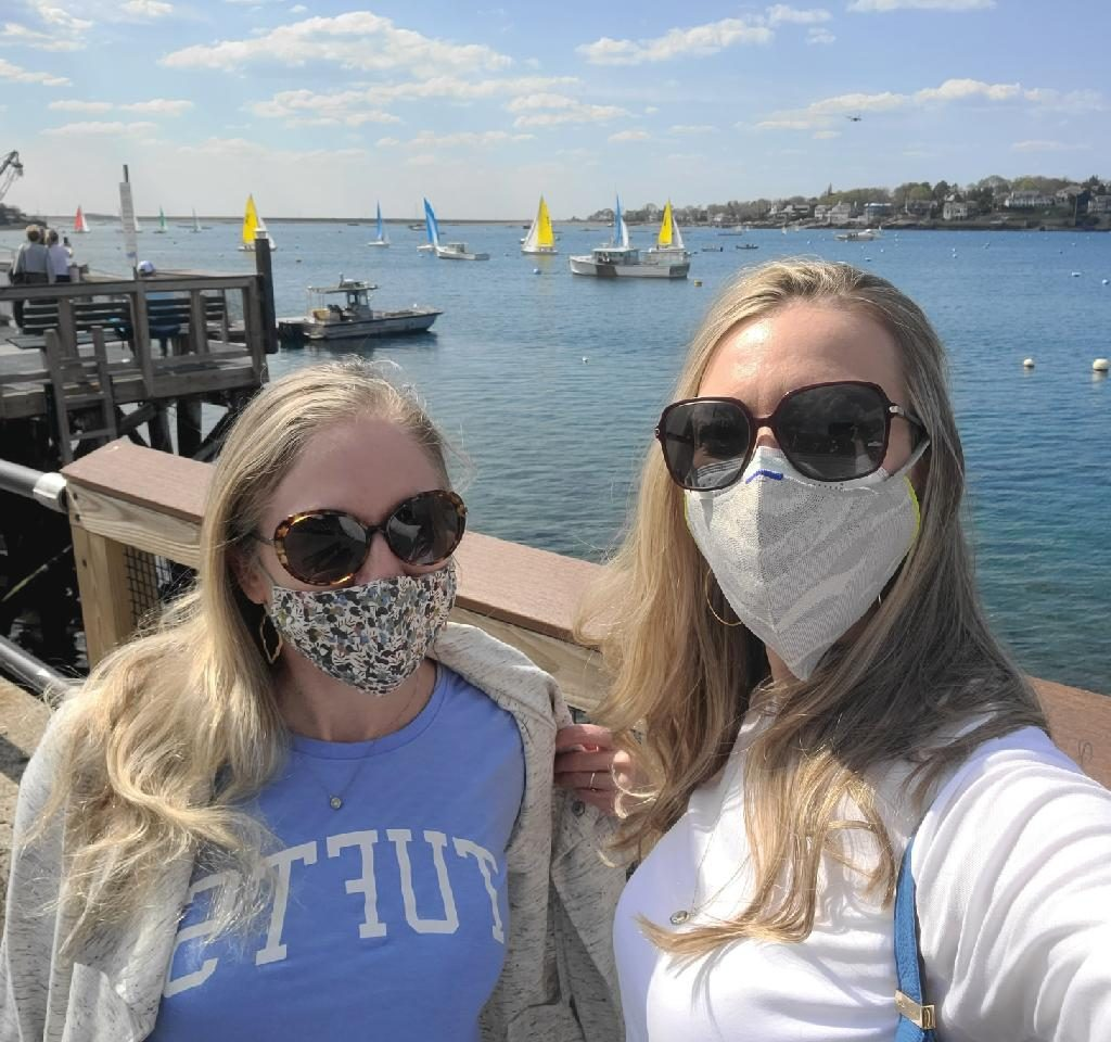 Melissa D. and Sarah W. stand for a selfie photo alongside the Boston harbor.