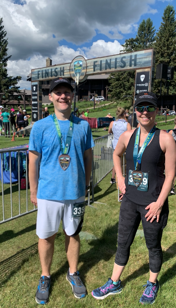 GBA students Mat G. and Amy W. pose for a picture in front of the finish line at the Glacier Half Marathon.
