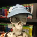 Leo the Skeleton model smiling at the camera, wearing a light blue Tufts Alumni visor, with a button pinned to it of The Block