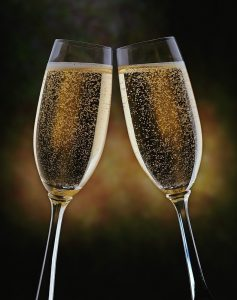 Two champagne glasses touch