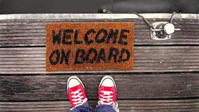 "Image: feet in front of a mat that reads ""welcome on board"""