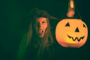 Woman dressed as a witch holding a lighted pumpkin