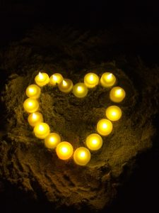 A heart shape made out of candles in the sand
