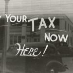 "A window with ""Pay Your Tax Now Here"" painted on it."