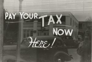 "A window with ""Pay Your Taxes Here"" painted on it."