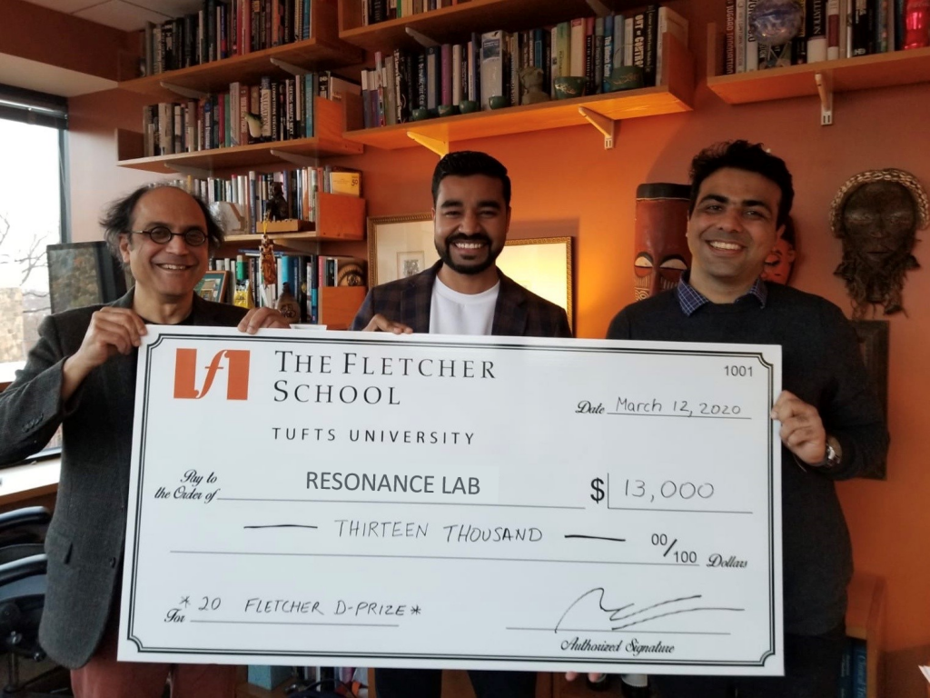 Three men are shown with a large check for 13,000 dollars in seed capital.