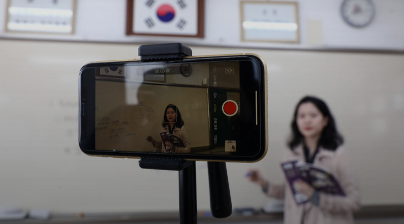 A teacher prepares lesson with a cell phone on the first day of online class in an empty classroom as South Koreans take measures to protect themselves against the spread of coronavirus.