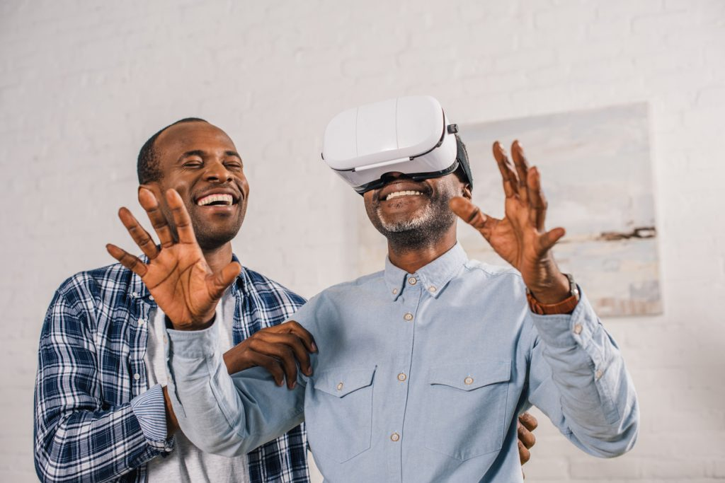 a son showing his father how to use a VR headset