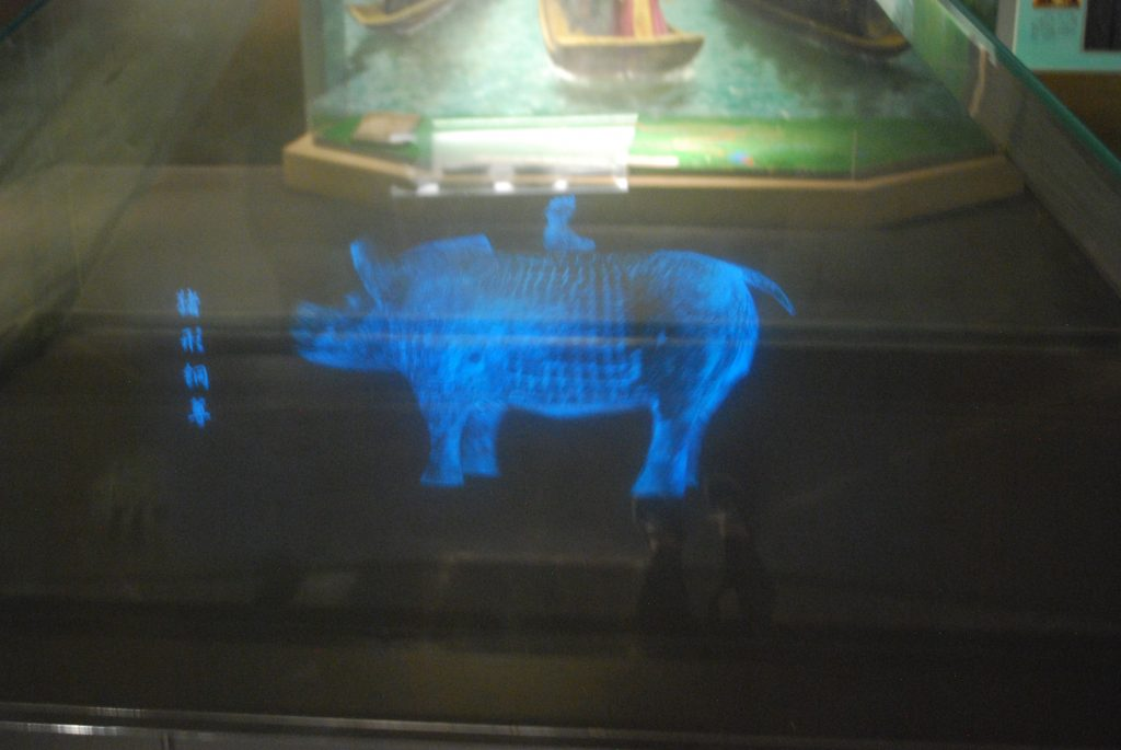 Small projection of a pig statue that rotates for visitors to see all sides of the object.