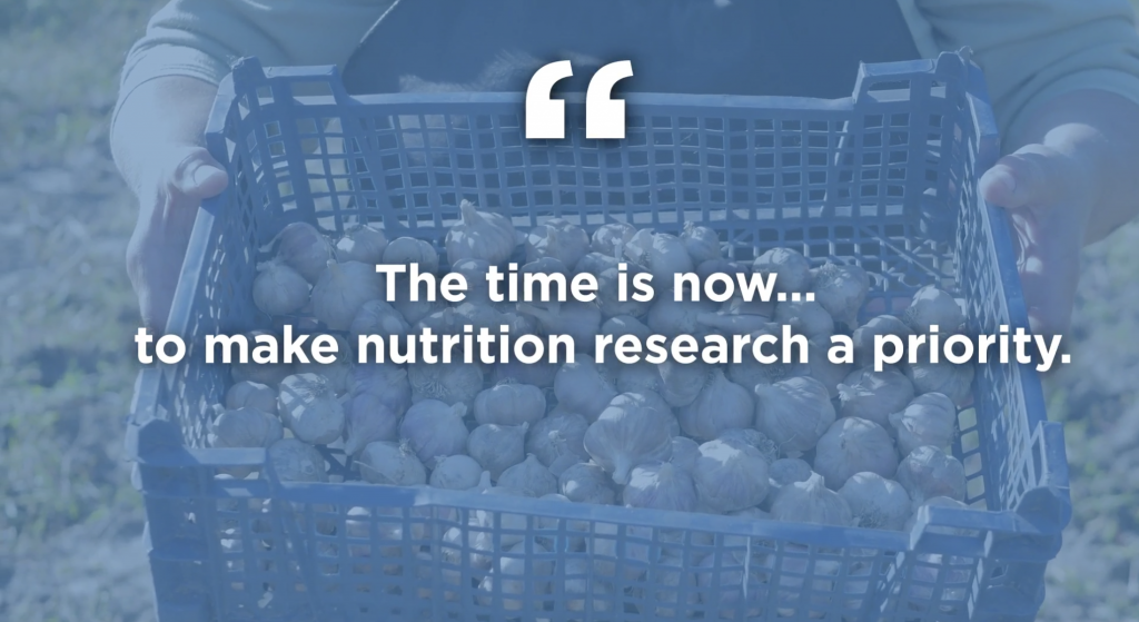 A blue-tinted photo of a basket of harvested brussels sprouts is overlaid with a quote that says the time is now to make nutrition research a priority