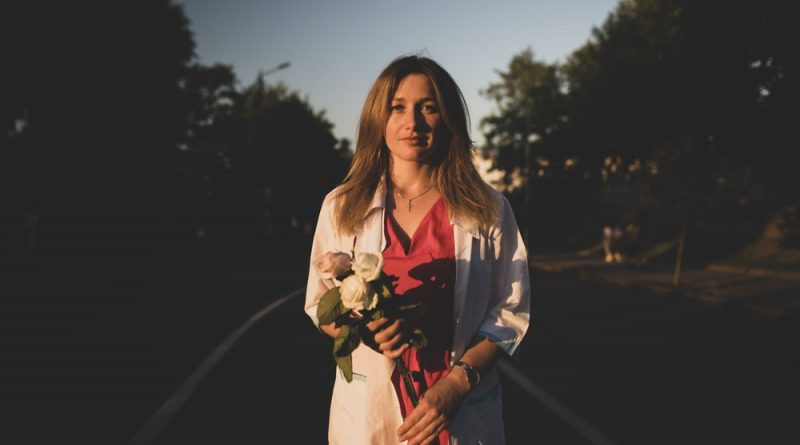 Photo depicts a woman dressed in a white jacket and a red shirt, holding white roses.