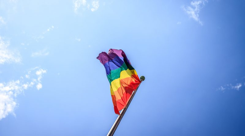 Pride flag against the background of a cloudless blue sky.
