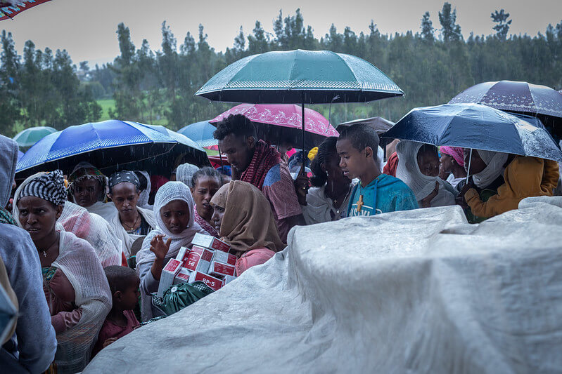 Ethiopians lining up in rain for food and supplies.