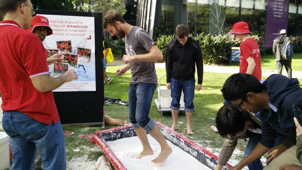 Andrew DB jumps around on a pool of oobleck, while Chris gets ready to take his turn, and Pat explains the phenomenon to an onlooking UNSW student.