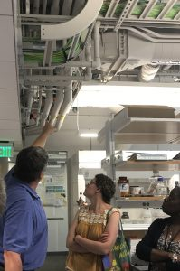 One of the tour guides, elliott miller, points to the exposed piping in the ceiling to explain the air ventilation systems in a lab